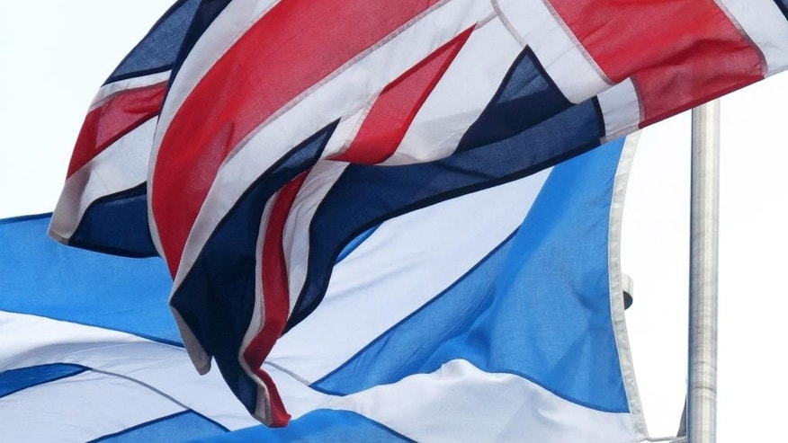 "In this photo taken March 16, 2014 the 'Saltire' flag, of Scotland, at rear, flies alongside the 'Union Jack' of the United Kingdom outside the Scottish Parliament in Edinburgh, Scotland. Scotland's swithering ""middle million"" has Britain's future in its hands. ""Swithering"" means wavering, and it's a word you hear a lot in Scotland right now. Six months from Tuesday, Scottish voters must decide whether their country should become independent, breaking up Great Britain as it has existed for 300 years. Faced with the historic choice, many find their hearts say ""aye"" but their heads say ""why risk it?"" Polls suggest as many as a quarter of Scotland's 4 million voters remain undecided, and their choice will determine the outcome. Many long to cut the tie binding them to England, but fear the risks _ and the financial fallout. (AP Photo/Jill Lawless)"
