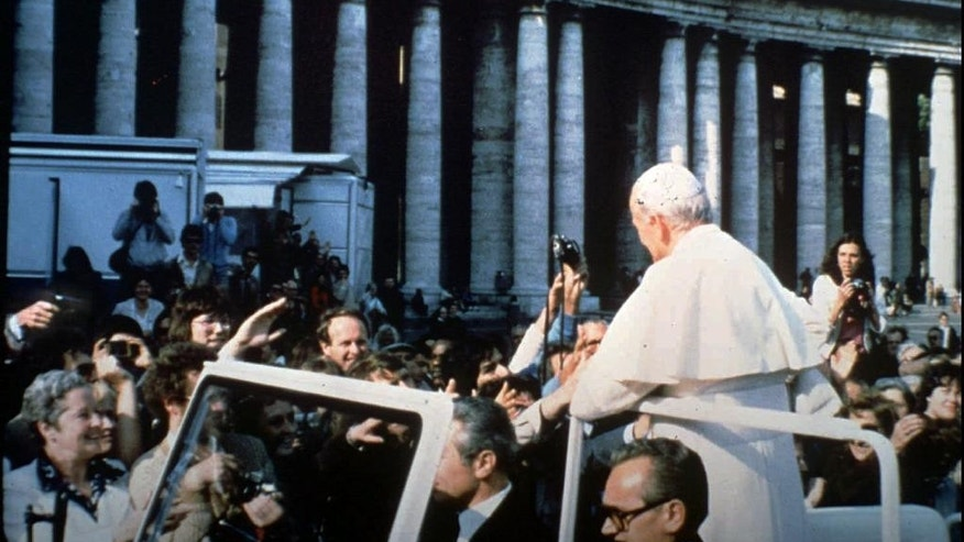 In this May 13, 1981 file photo provided by Vatican paper L'Osservatore Romano, Mehmet Ali Agca, left, holds a Browning HP 9mm handgun to shoot Pope Jonh Paul II at the Vatican. Alitalia Flight 488 landed in Krakow, Poland on Tuesday, March 18, 2014 with some very special cargo on board: The gun used to shoot Pope John Paul II. Monsignor Dariusz Ras, the Polish priest who runs the John Paul II museum in the late pope's childhood home in Wadowice, transported the pistol from Rome to Poland for the museum's upcoming exhibit in honor of John Paul's April 27 canonization, Alitalia said. Mehmet Ali Agca used the Browning HP 9mm handgun to shoot John Paul in the abdomen in St. Peter's Square on May 13, 1981. The pope spent nearly three weeks in the hospital recovering. (AP Photo/L'Osservatore Romano)