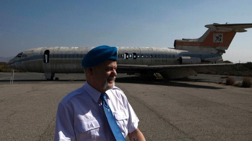 Canadian veteran soldier Gary Best who has served with the United Nations Peacekeeping force on war-divided Cyprus stands in front of an abandoned passenger aircraft, at the derelict Nicosia airport located inside the UN-controlled buffer zone on the capital's outskirts on Tuesday, March 18, 2014. A gutted Cyprus Airways Trident passenger jet a stone's throw away from the terminal serves a reminder of the fierce battles that had raged there in July, 1974. Advancing Turkish forces had tried to seize the strategically important airport on the capital's western outskirts, hours in to their invasion of Cyprus that was triggered by a coup aimed at uniting the island with Greece. Canadian soldiers then serving with the United Nations Peacekeeping force in Cyprus _ or UNFICYP _ helped repel the advance. Since then, it's been the force's headquarters midway through a 180 kilometer (112 mile) buffer zone that splits this ethnically divided island into a breakaway Turkish Cypriot north and a internationally recognized, Greek Cypriot south. (AP Photo/Petros Karadjias)