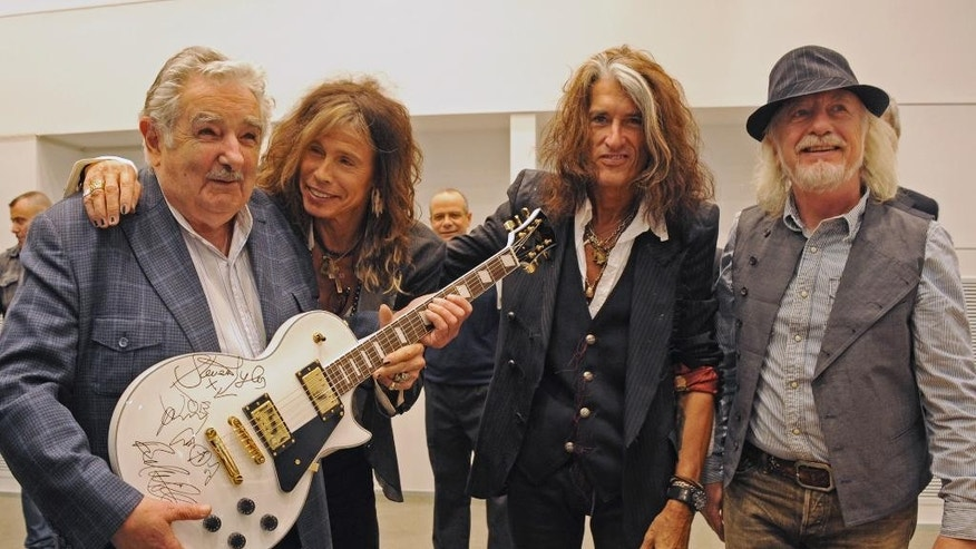 "FILE - In this Oct. 8, 2013 file photo released by Uruguay's Press Office, President Jose Mujica, left, poses with Aerosmith's band members Steven Tyler, second from left, Joe Perry, second from right, and Brad Whitford after receiving an autographed guitar as a gift at presidential house in Montevideo, Uruguay. While outside his country he is an international figure, well known for his modest lifestyle, consistent with his ideals and his good-nature, among his own people Uruguay's President known as ""Pepe"" does not generate such devotion and many question his management. (AP Photo/Uruguay Press Office, Alvaro Salas, File)"