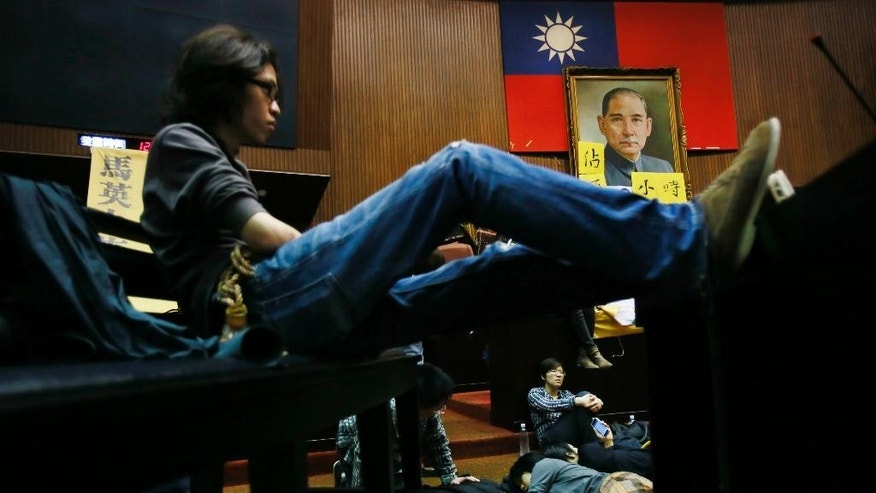 Student protesters against a China Taiwan trade agreement occupy the floor of the legislature after a night of scuffling with police in Taipei, Taiwan, Wednesday, March 19, 2014. Several hundred opponents of a far-reaching trade pact with China occupied Taiwan's legislature late Tuesday, further delaying action on a measure that Beijing strongly favors. (AP Photo/Wally Santana)