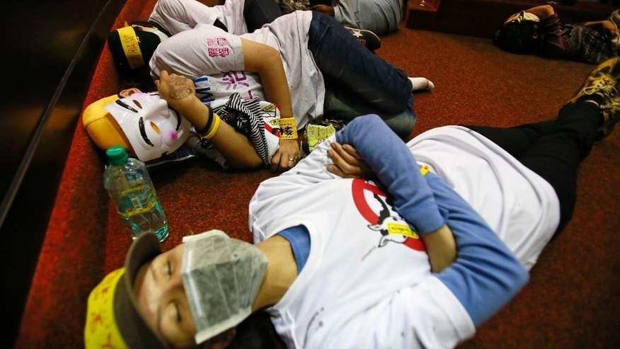 Student protesters against a China Taiwan trade agreement sleep on the floor of the legislature after a night of scuffling with police in Taipei, Taiwan, Wednesday, March 19, 2014. Several hundred opponents of a far-reaching trade pact with China occupied Taiwan's legislature late Tuesday, further delaying action on a measure that Beijing strongly favors. (AP Photo/Wally Santana)