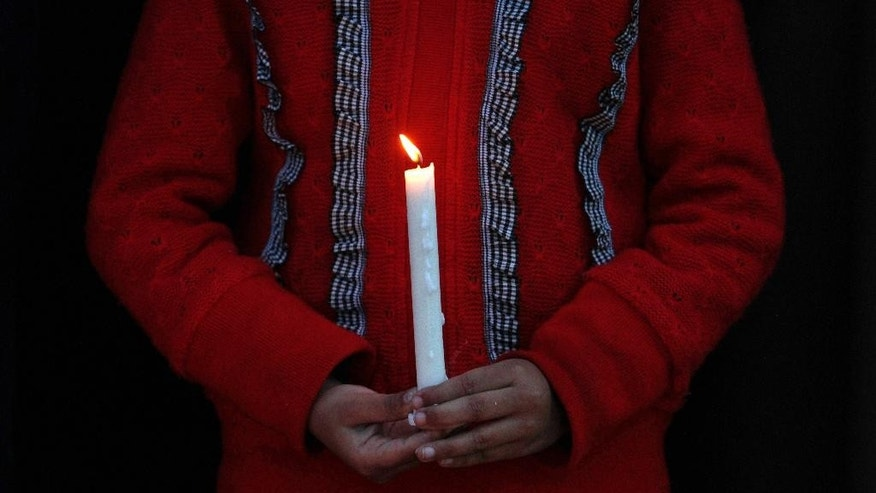 A girl takes part in a candlelight vigil organized by a social group, the Christian Muslim Alliance Pakistan, for passengers that were aboard a missing Malaysia Airlines plane  Tuesday, March 18, 2014 in Islamabad, Pakistan. The search for Malaysian Flight 370, which vanished early March 8, 2014 while flying from Kuala Lumpur to Beijing with 239 people on board, has now been expanded deep into the northern and southern hemispheres. (AP Photo/Anjum Naveed)