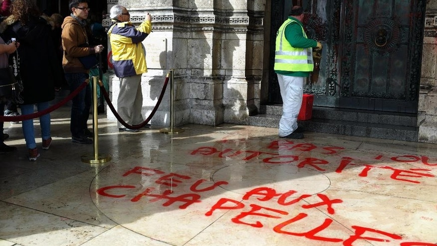 A worker cleans the graffiti at entrance  of the Sacre Coeur basilica in the Montmartre district of Paris, Wednesday, March 19, 2014. There were no immediate claims of responsibility for graffiti found at the iconic basilica. Graffiti on the floor reads: Down with any authority. (AP Photo/Thibault Camus)