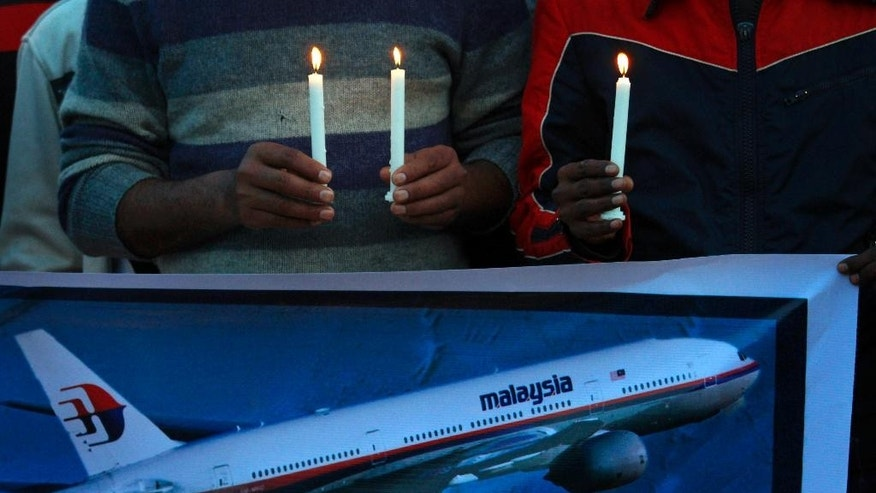 Members of the social group Christian Muslim Alliance Pakistan take part in a candlelight vigil for passengers that were aboard a missing Malaysia Airlines plane, Tuesday, March 18, 2014 in Islamabad, Pakistan. The search for Malaysian Flight 370, which vanished early March 8, 2014 while flying from Kuala Lumpur to Beijing with 239 people on board, has now been expanded deep into the northern and southern hemispheres. (AP Photo/Anjum Naveed)