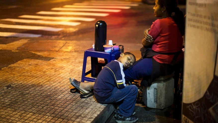 A child sleeps on the legs of his mother, who sells coffee in downtown Caracas, on March 4, 2014.