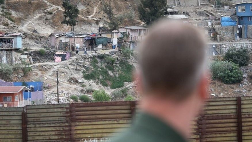 "SAN DIEGO, CA - OCTOBER 03:  A U.S. Border Patrol agent looks into Tijuana, Mexico from the American side of the U.S.-Mexico border fence on October 3, 2013 near San Diego, California. While hundreds of thousands of government workers were furloughed due to the federal shutdown, thousands of Border Patrol agents, air-traffic controllers, prison guards and other federal employees deemed ""essential"" remain on duty, although their pay may be delayed.  (Photo by John Moore/Getty Images)"