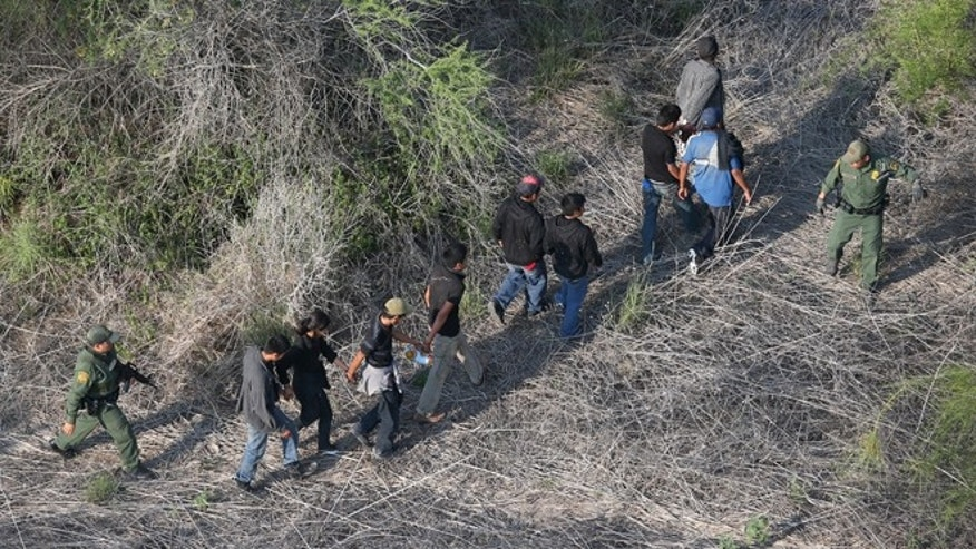HAVANA, TX - MAY 20:  U.S. Border Patrol agents escort a group of undocumented immigrants into custody with helicopter support from the U.S. Office of Air and Marine on May 20, 2013 near the U.S.-Mexico border in Havana, Texas. The Rio Grande Valley area has become the busiest sector for illegal immigration on the whole U.S.-Mexico border with more than a 50 percent increase in the last year.  (Photo by John Moore/Getty Images)
