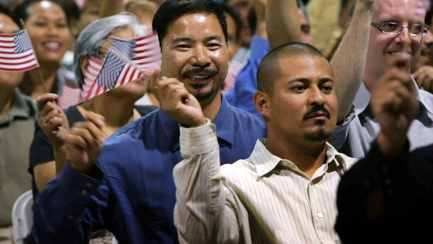 POMONA, CA - JULY 26:  Immigrants wave flags after being sworn in as U.S. citizens in naturalization ceremonies on July 26, 2007 in Pomona, California. Some of the 6,000 people taking their citizenship oath are part of a flood of immigrants trying to beat a July 30 deadline when the cost of becoming a citizen goes up. First-time green card will go from $325 to $1,010, temporary resident status will increase from $255 to $710, and naturalization will cost $300 more. To meet the flood of immigrant applications, immigration offices had to extend their office hours.  (Photo by David McNew/Getty Images)