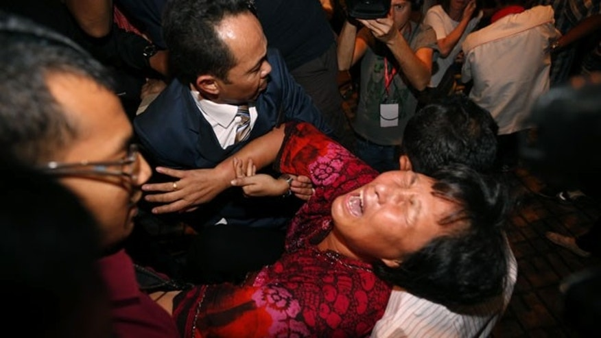 March 19, 2014: A Chinese relative of a passenger aboard a missing Malaysia Airlines plane is carried out by security officials as she protests before a press conference at a hotel in Sepang, Malaysia. (AP Photo/Vincent Thian)