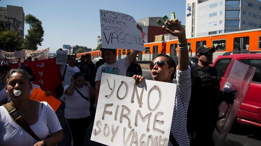 "In this March 5, 2014 photo, Mexico City subway vendors, known ""Vagoneros"" protest, with a sign that reads in Spanish ""I did not sign, I'm Vagonero"". For years, Mexico City's subway was a wild ride, a combination of street theater and open-air market in closed, packed train cars. City officials have now kicked off the informal vendors and beggars to make public transit more civilized. But the vendors are marching and demanding the right to remain, saying they have no other way to work. (AP Photo/Eduardo Verdugo)"