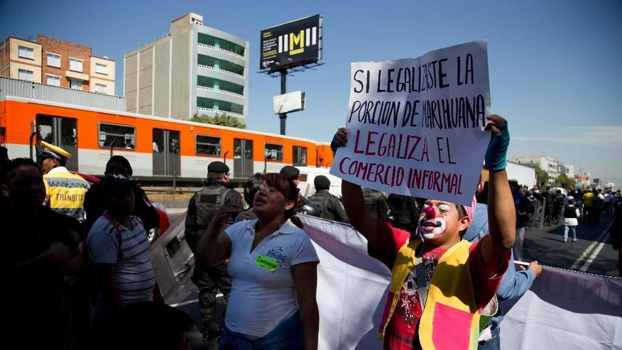 "In this March 5, 2014 photo, a Mexico City subway vendor, known localy as ""Vagonero"" protests in Mexico City, dressed as a clown with a sign that reads ins Spanish ""If you legalized marijuana, legalize informal work"". For years, Mexico City's subway was a wild ride, a combination of street theater and open-air market in closed, packed train cars. City officials have now kicked off the informal vendors and beggars to make public transit more civilized. But the vendors are marching and demanding the right to remain, saying they have no other way to work. (AP Photo/Eduardo Verdugo)"
