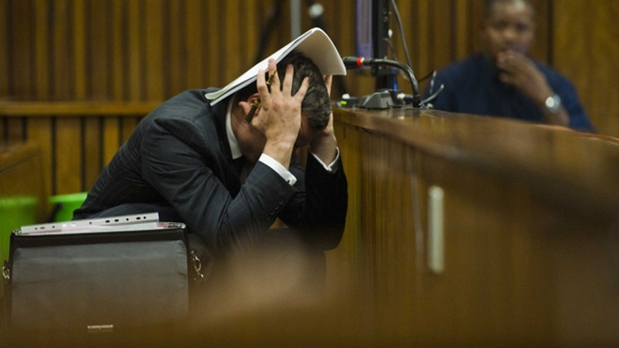 March 13, 2014: Oscar Pistorius covers his head with his hands and a notebook as he listens to forensic evidence during his trial in court in Pretoria, South Africa.