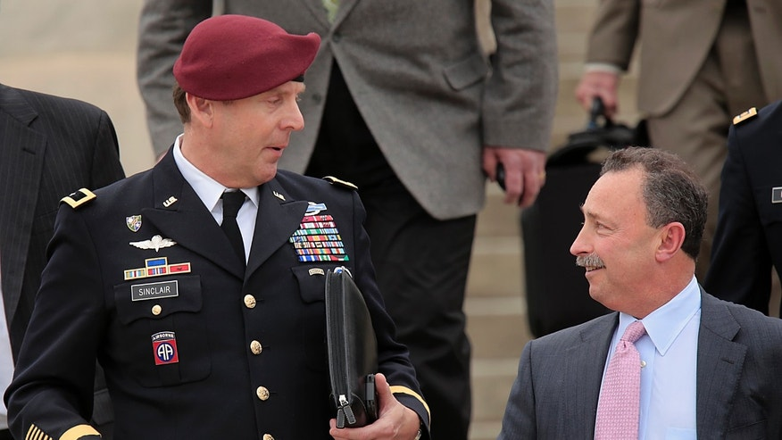 Brig. Gen. Jeffrey Sinclair, left, leaves court at Fort Bragg, N.C., Wednesday, March 19, 2014.