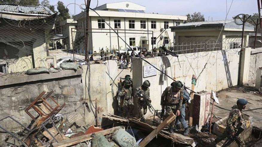 March 20, 2014: Afghan Army soldiers and police search through a police station after the Taliban staged a multi-pronged attack on a police station in Jalalabad, eastern Afghanistan. Taliban insurgents staged the attack, using a suicide bomber and gunmen to lay siege to the station, government officials said. Two remotely detonated bombs also exploded nearby. (AP Photo/Rahmat Gul)