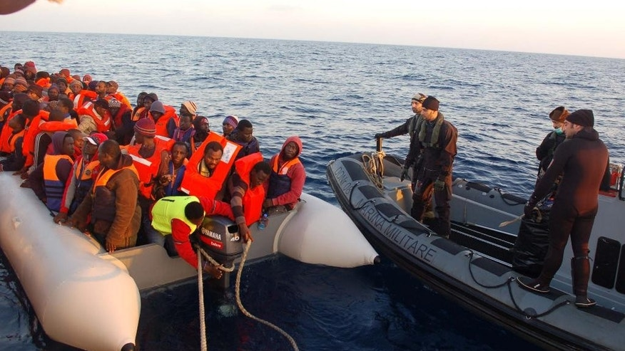 In this photo released by the Italian Navy Thursday, March 20, 2014, migrants stand on a dinghy after being rescued along the Mediterranean sea. Italian authorities say they have rescued more than 4,000 would-be migrants at sea over the past four days as the war in Syria and instability in Libya spawn new waves of refugees. The numbers of migrants reaching Italian shores generally rises as warm weather and calm seas make the Mediterranean Sea crossing from North Africa easier. But the U.N. refugee agency says the 2014 numbers represent a 300 percent increase over the same period in 2013. (AP Photo/Italian Navy)