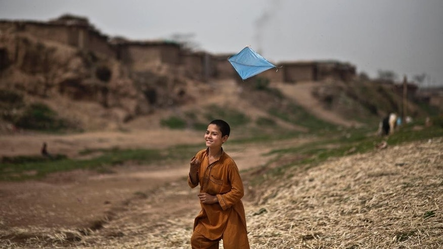 An Afghan refugee boy, plays with a kite, in a poor neighborhood on the outskirts of Islamabad, Pakistan, Thursday, March 20, 2014. The United Nations has proclaimed that March 20 is the International Day of Happiness. (AP Photo/Muhammed Muheisen)