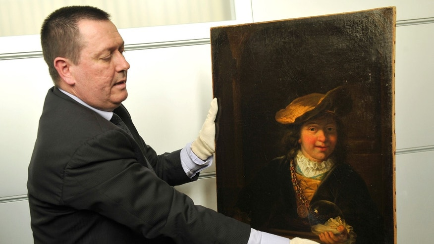 "March 20, 2014 - Policeman Colonel Stephane Gauffeny presents to the press Rembrandt's painting ""Child with a Soap Bubble,"" stolen in 1999 from the municipal museum of Draguignan, southeastern France. he Rembrandt painting worth millions has been recovered in Nice, and two people found in possession of the Dutch master's painting have been arrested."