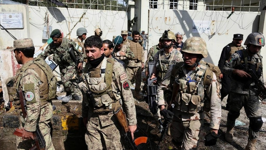 Afghan Army and police search through a police station after the Taliban staged a multi-pronged attack on a police station in Jalalabad, eastern Afghanistan, Thursday, March 20, 2014. Taliban insurgents staged the attack, using a suicide bomber and gunmen to lay siege to the station, government officials said. Two remotely detonated bombs also exploded nearby. (AP Photo/Rahmat Gul)