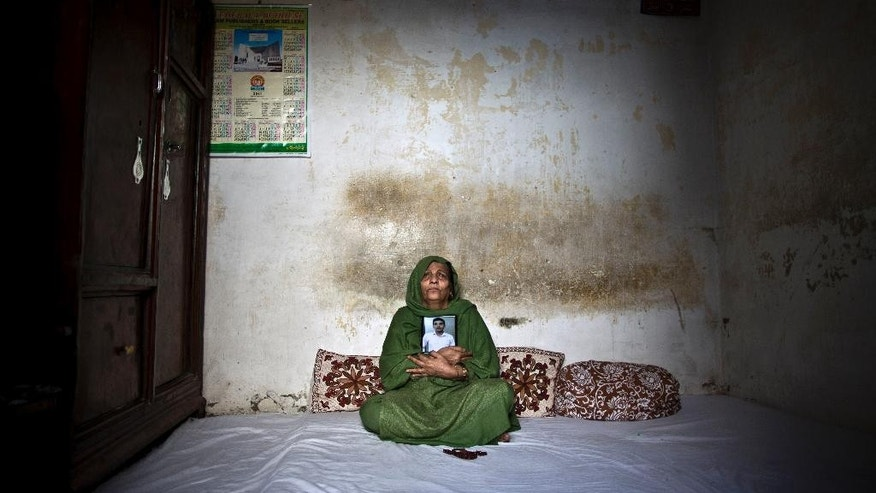 "In this Tuesday, March 18, 2014 photo, Pakistani Salima Akhtar, 65, mother of Akmal Omar, 21, who was one of eleven victims that was killed by suicide bombers in an attack on a court complex on the 3rd of March 2014, grieves while embracing his photograph in his bedroom, in Rawalpindi, Pakistan. ""They ripped my heart from my chest, how can I live after you my Akmal,"" Salima said. (AP Photo/Muhammed Muheisen)"