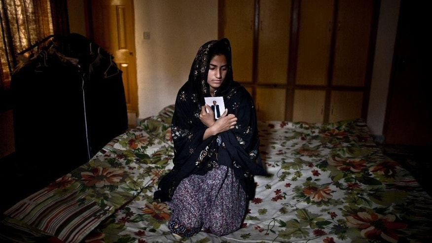 "In this Sunday, March 16, 2014 photo, Pakistani Syeda Aima Tanveer, 20, daughter of lawyer Tanveer Haider, 58, who was one of eleven victims that was killed by suicide bombers in an attack on a court complex on the 3rd of March 2014, sits on her father's bed embracing his photograph, at their home on the outskirts of Islamabad, Pakistan. ""My father, my hero, I miss you so much father,"" Aima said. (AP Photo/Muhammed Muheisen)"