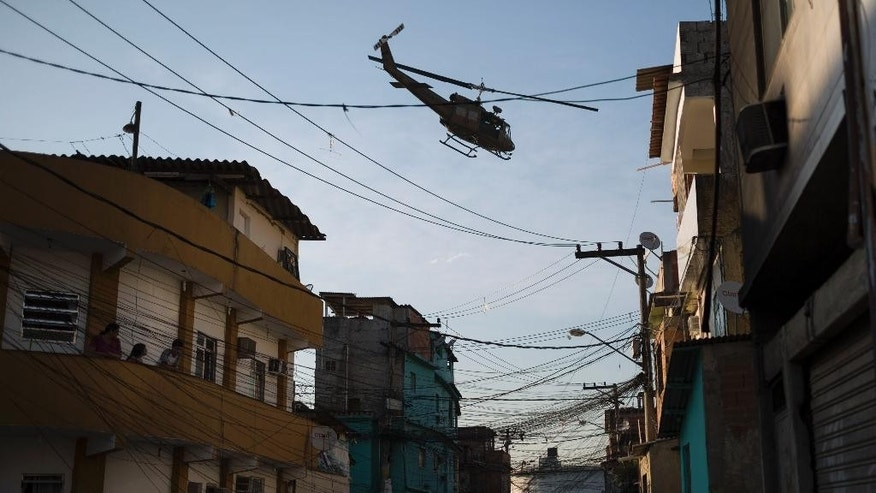 A military police helicopter flies over the Mandela shantytown, part of the Manguinhos slum complex, after attacks to their Pacifying Police Unit posts in Rio de Janeiro, Brazil, Friday, March 21, 2014. Rio de Janeiro police say suspected drug gang members on Thursday night attacked three police slum outposts and burned one of them. Officials say they'll ask for elite Brazilian federal police to help quell a wave of violence in supposedly pacified slums. (AP Photo/Felipe Dana)