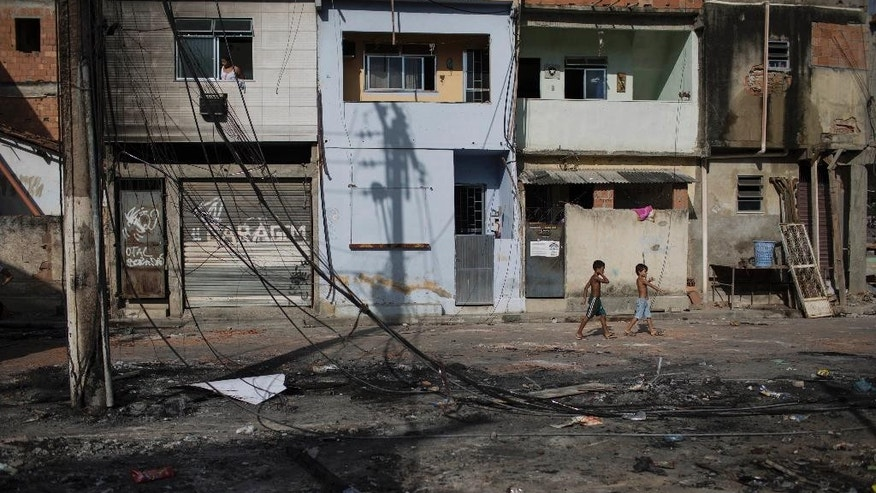 Children walk past what remains of a Pacifying Police Unit post at the Mandela shantytown, part of the Manguinhos slum complex, in Rio de Janeiro, Brazil, Friday, March 21, 2014. Rio de Janeiro police say suspected drug gang members on Thursday night attacked three police slum outposts and burned one of them. Officials say they'll ask for elite Brazilian federal police to help quell a wave of violence in supposedly pacified slums. (AP Photo/Felipe Dana)