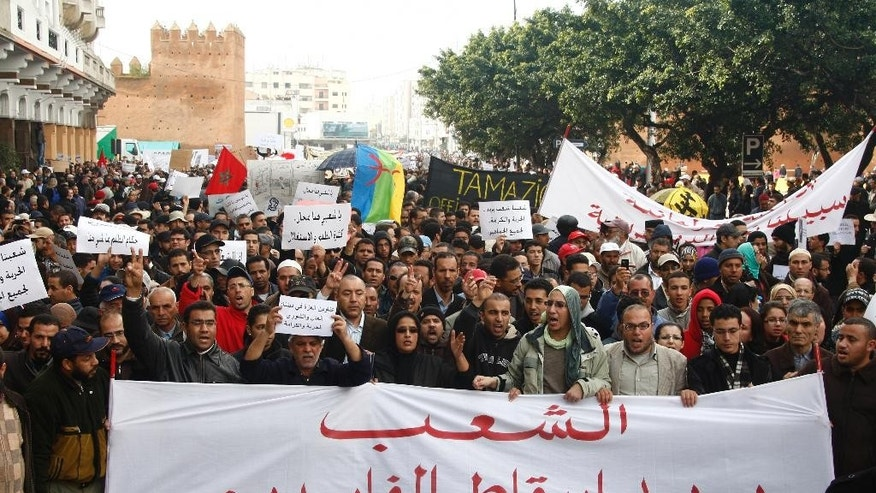 "FILE - In this Sunday, Feb 20, 2011 file photo, pro-democracy protesters demonstrate in Rabat, Morocco,  carrying a banner reading ""the people want the fall of the corrupt."" The Islamist party that dominated elections in 2011 ran on an anti-corruption platform but two years later, despite its rhetoric, it has been business as usual for corruption in Morocco. (AP Photo/Abdeljalil Bounhar, File)"
