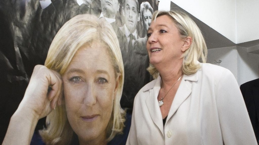 FILE - - In this March 8, 2014 file photo, French far-right party leader  Marine Le Pen walks past a poster of her at the party headquarters in Henin-Beaumont, northern France, as part of the municipal campaign. Marine Le Pen sees political gold in the abandoned coal mines of northern France that once pumped life, jobs and an identity into places like Henin-Beaumont, a bleak town that the far-right leader says is the avant-garde of her anti-immigration party's march to power. (AP Photo/Jacques Brinon, File)