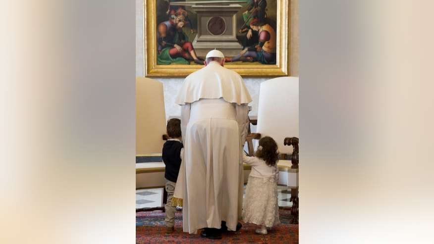 Pope Francis holds by their hands Luca, left, and Giorgia May, grandchildren of Malta's President George Abela, during a private audience in the Pontiff's studio, at the Vatican, Friday, March 21, 2014. (AP Photo/Andrew Medichini, Pool)