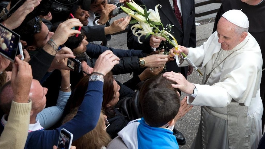 Pope Francis is cheered by faithful as he arrives for a meeting with relatives of innocent mafia victims, in Rome's St. Gregorio VII church, just outside the Vatican, Friday, March 21, 2014. (AP Photo/Andrew Medichini)