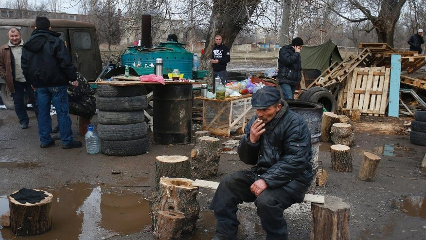 Pro Russian activists camped near the armory of Ukrainian army in a bid to prevent the export of arms and ammunition in the village of Poraskoveyevka, eastern Ukraine, Thursday, March 20, 2014. The disheveled men barricading the muddy lane leading into a military base in this eastern Ukraine village say they're taking a stand to defend Russian-speakers. (AP Photo/Sergei Grits)