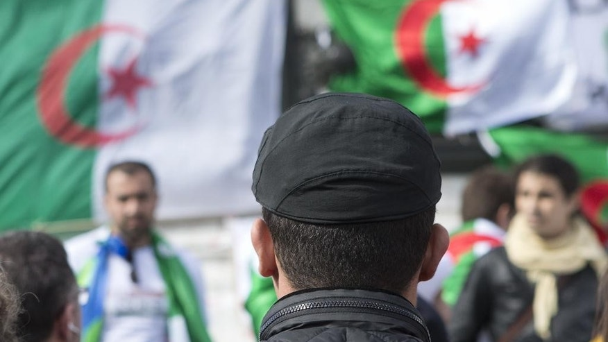 Protesters stand in front of national flags during a rally against current Algerian President Abdelaziz Bouteflika, Saturday, March 22, 2014 in Paris. Demonstrators called for a boycott of the upcoming presidential election as twelve candidates have registered for Algeria's April 17 presidential election including Bouteflika, 77, who is running for a fourth term. (AP Photo/Jacques Brinon)