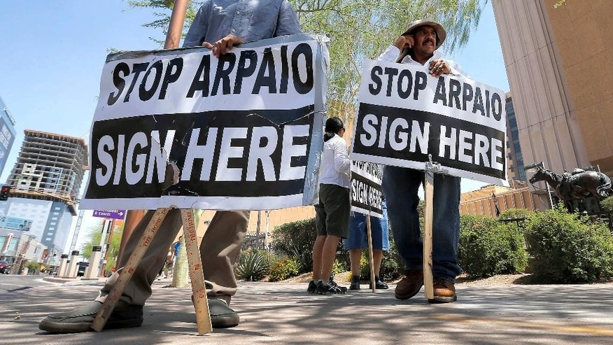 FILE - In this May 29, 2013, file photo, Simon Lopez, left, and Hiliaro Islas hold signs while trying to collect signatures in an effort to recall Maricopa County Sheriff Joe Arpaio, in downtown Phoenix. Arizona is still widely viewed in Mexico as the most anti-Mexico state in the U.S., even if the tough anti-migrant law behind that perception has been largely voided. But Arizona's leaders are logging lots of miles to put a new face on their home state. (AP Photo/Matt York, File)