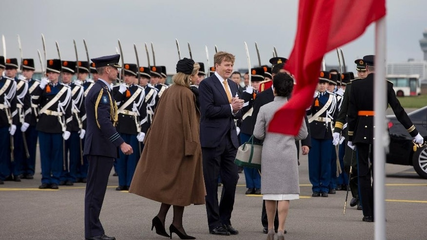 China's President Xi Jinping, behind the Chinese flag, his wife Peng Liyuan, in grey coat, Dutch King Willem Alexander, center, and his wife Queen Maxima, in brown coat, talk after inspecting the honor guard upon Xi's arrival at Schiphol Amsterdam airport, Netherlands, Saturday March 22, 2014. Xi is on a two-day state visit ahead of the March 24 and 25 Nuclear Security Summit in The Hague. (AP Photo/Peter Dejong, Pool)