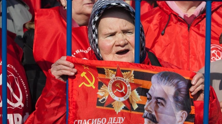 An elderly Russian Communist party supporter holds up a portrait of Soviet dictator Josef Stalin with a Soviet Union sign during a rally in support of Crimea joining Russia near the Red Square in Moscow, Russia, on Saturday, March 22, 2014. Moscow on Friday formally sealed Crimea's annexation, less than a week after a referendum where Crimeans overwhelmingly voted to join Russia. (AP Photo/Alexander Zemlianichenko Jr)
