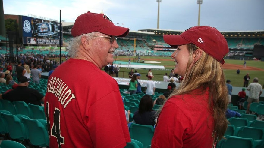 Bob Wardle, left, and his daughter Liz Sargant arrive at the Sydney Cricket Ground where the Major League Baseball opening game between the Los Angeles Dodgers and Arizona Diamondbacks is scheduled in Sydney, Saturday, March 22, 2014.  (AP Photo/Rick Rycroft)