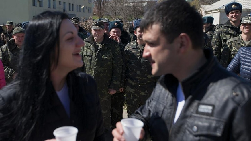 Ukrainian airmen smile as Lieutenants Galina Volosyanchik, left, and Ivan Benera, right, prepare to kiss each other as they celebrate their wedding at the Belbek airbase outside Sevastopol, Crimea, on Saturday, March 22, 2014. Two young Lieutenants got married today and arrived to their unit for a short celebration as Russian troops continue to occupy part of the airbase and demand surrender of Ukrainian airmen. (AP Photo/Ivan Sekretarev)