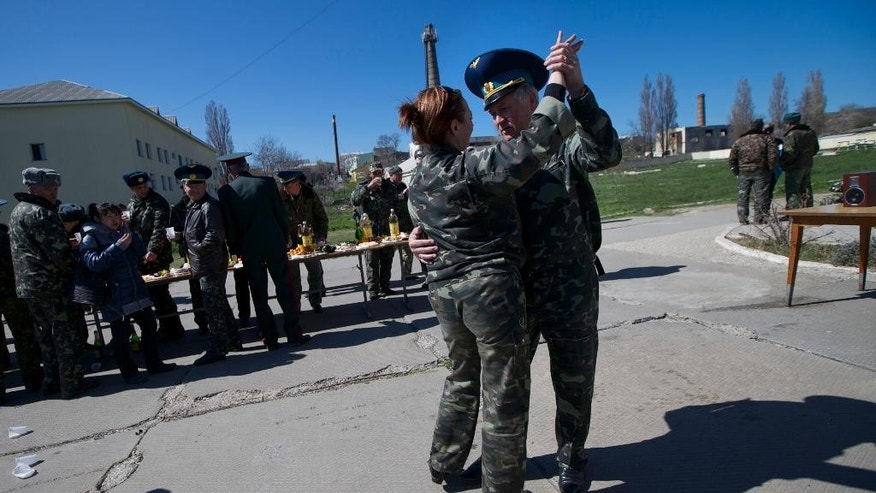 Ukrainian airmen dance as they celebrate their comrade's wedding at the Belbek airbase outside Sevastopol, Crimea, on Saturday, March 22, 2014. Two young Lieutenants, medic Galina Volosyanchik and communication officer Ivan Benera got married today and arrived to their unit for a short celebration as Russian troops continue to occupy part of the airbase and demand surrender of Ukrainian airmen. (AP Photo/Ivan Sekretarev)