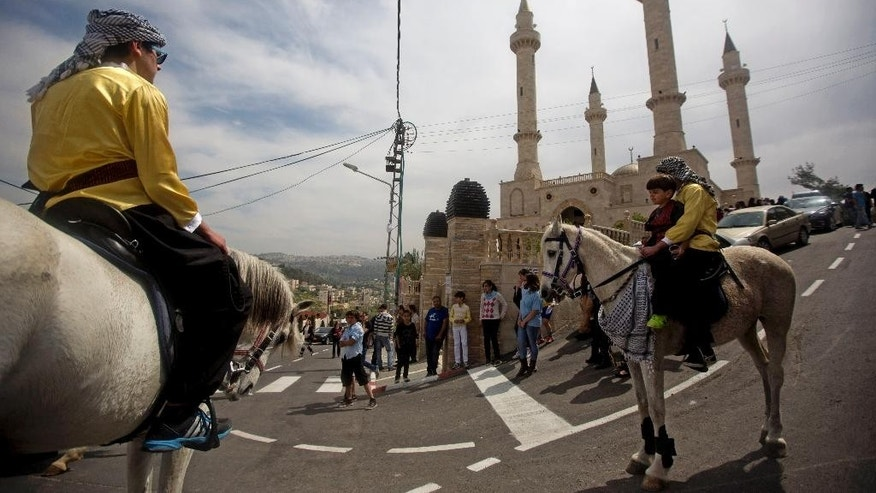 Palestinian ride their horses near a new mosque, partially funded by Chechnya, in the Arab village of Abu Ghosh, on the outskirts of Jerusalem, Sunday, March 23, 2014. Isa Jabar, the mayor of the village, says Chechnya donated $6 million for the new mosque and that some Abu Ghosh residents trace their ancestry to 16th century Chechnya and the Caucus region. (AP Photo/Sebastian Scheiner)