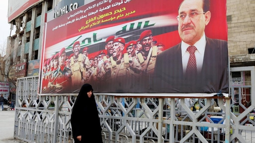 "In this Tuesday, March 18, 2014 photo, an Iraqi woman walks past an anti-terrorism banner with a photo of Iraqi Prime Minister Nouri al-Maliki, in Baghdad, Iraq. Islamic militants who took over the Iraqi city of Fallujah are now trying to show they can run it, providing social services, policing the streets and implementing Shariah rulings in a bid to win the support of its Sunni Muslim population. Partial translation of Arabic on banner reads, ""the media supports security forces efforts to capture terrorists and resume safety."" (AP Photo/Karim Kadim)"