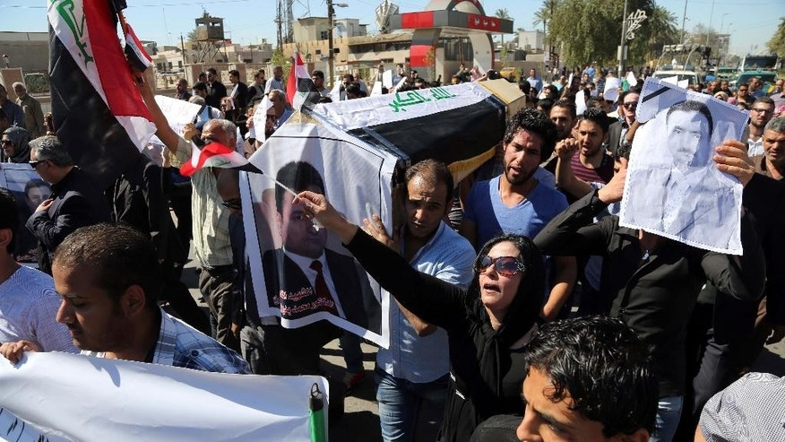 Mourners chant slogans during a symbolic funeral for the bureau chief of a local radio station in Baghdad, Iraq, Sunday, March 23, 2014. A junior officer working for Iraqi President Jalal Talabani, also an ethnic Kurd, shot dead Mohammed Bdaiwi, a well-known radio journalist during a quarrel Saturday near the leader's east Baghdad residence, police said. (AP Photo/Karim Kadim)