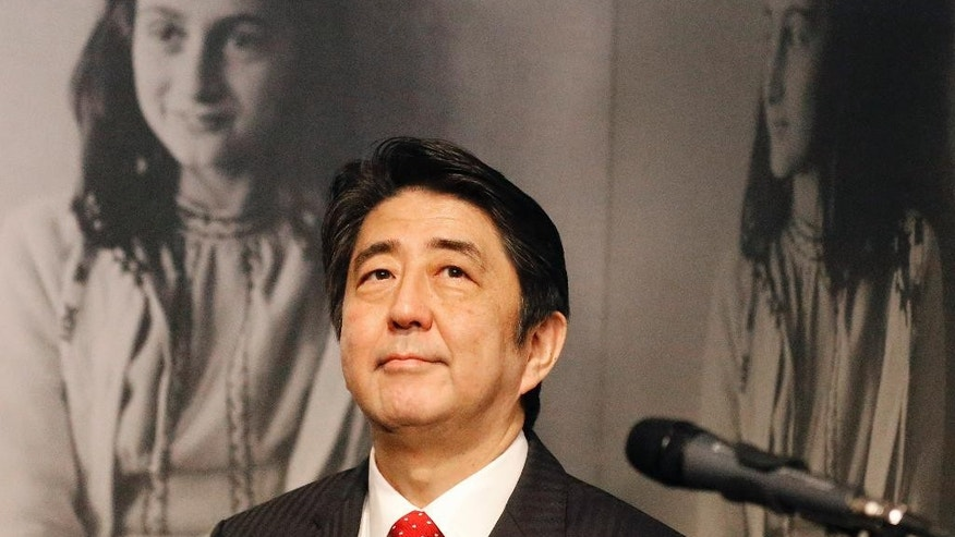 Japan's Prime Minister Shinzo Abe looks at pictures of Anne Frank, rear, as he visits the Anne Frank House museum in Amsterdam, Netherlands, Sunday, March 23, 2014. Abe expressed regrets that 300 copies of Anne Franks' diary were vandalized recently in Tokyo libraries. (AP Photo/Frank Augstein)
