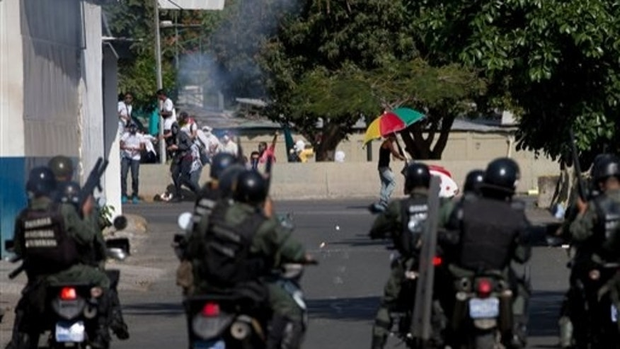 Anti-government protesters take cover from tear gas fired by Bolivarian National guards riding motorbikes during clashes in Caracas, Venezuela, Saturday, March 22, 2014. Two more people were reported dead in Venezuela as a result of anti-government protests even as supporters and opponents of President Nicolas Maduro took to the streets on Saturday in new shows of force. (AP Photo/Fernando Llano)