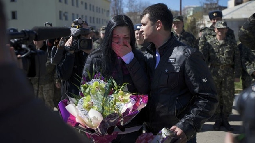 March 22, 2014: Galina Volosyanchik, center left, and Ivan Benera, center right, react as they are welcomed by senior officers and comrades celebrating their wedding at the Belbek airbase outside Sevastopol, Crimea. (AP Photo/Ivan Sekretarev)