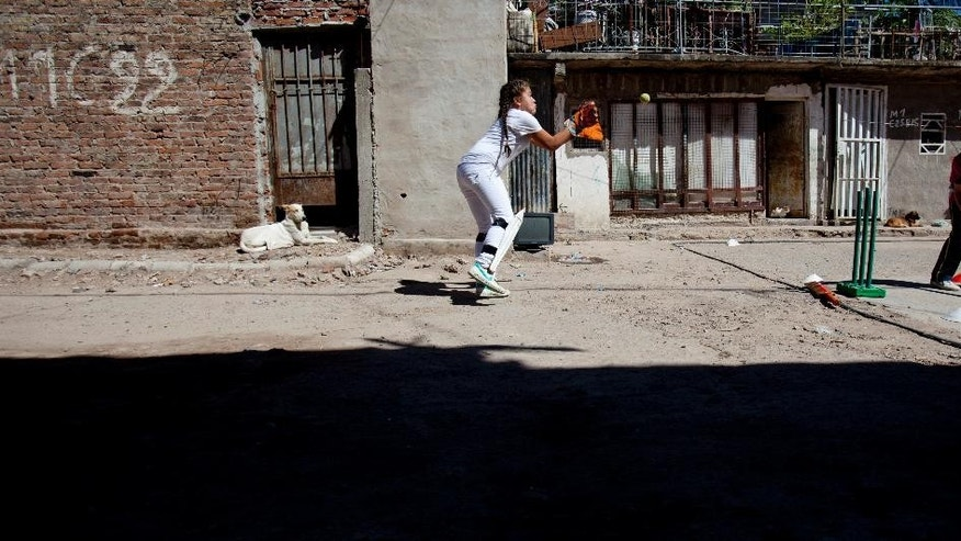 Milagros Mendez, left, catches a ball during a Caacupe cricket team training session at the Villa 21-24 slum  in Buenos Aires, Argentina, Saturday, March 22, 2014. The International Cricket Council has recognized the team, formed from the children of the Villa 21-24 shantytown, honoring them as a global example for expanding the sport, which in certain countries, like India, is widely played, but in many parts of the world restricted to elite sectors of society. Introducing cricket in the slum began in 2009 as an idea to transform the game into a social integration mechanism, before that it rarely breached the gates of the country's upscale private schools. (AP Photo/Natacha Pisarenko)