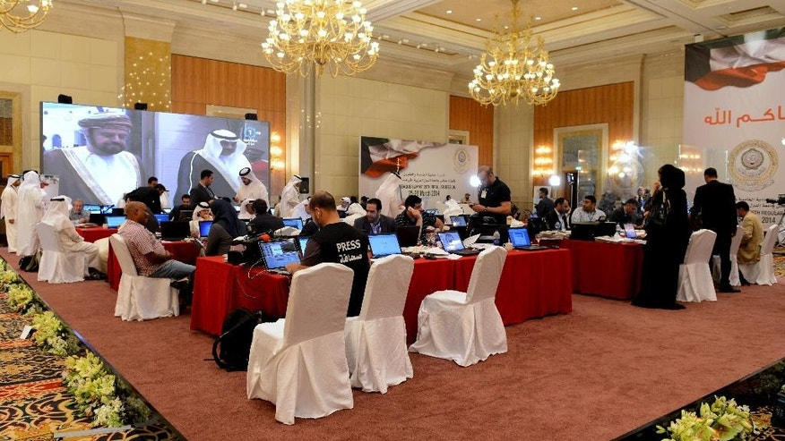 Journalists work in the Kuwait Ministry of Information's press center at the Al Raya ballroom in Kuwait City on Monday, March 24, 2014. The country is preparing to host the annual Arab League Summit scheduled for March 25 and 26.(AP Photo/Nasser Waggi)