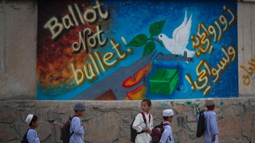 "In this Wednesday, March 12, 2014 photo, school children pass by a graffiti reading, ""ballot not bullet"" on their way back home on the outskirts of Kandahar, southern Afghanistan. Warlords with a violent past have played a role in influencing Afghan politics since a U.S.-led coalition helped oust the Taliban in 2001. But they are emerging to play an overt political role in next month's presidential elections as President Hamid Karzai leaves the scene. (AP Photo/Anja Niedringhaus)"