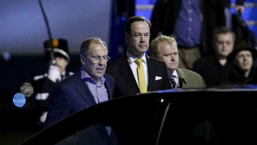 Russian Foreign Minister Sergey Lavrov, left, arrives at Schiphol Amsterdam airport, Netherlands, Sunday March 23, 2014, one day ahead of the March 24 and 25 Nuclear Security Summit. (AP Photo/Sean Gallup, Pool)