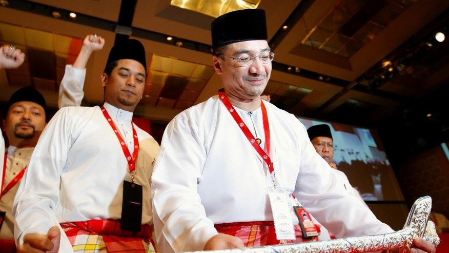 "FILE - In this Wednesday, March 25, 2009 file photo, Hishammuddin Hussein, front, chief of Youth wings placing the ""Malay Keris"" on a ceremonial display stand during the opening of United Malays National Organisation (UMNO) Youth general assemblies in Kuala Lumpur, Malaysia. Hishammuddin Hussein's wife is a princess. His cousin is prime minister, and he's been mentioned as a possible successor. But right now, as the face of his country's effort to find Malaysia Airlines Flight 370, he is the man who has delivered more than two weeks of frustrating news about one of the most confounding searches in aviation history. (AP Photo/Vincent Thian)"